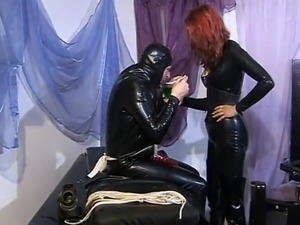 Two sexy femdoms in latex having fun punishing their horny slave