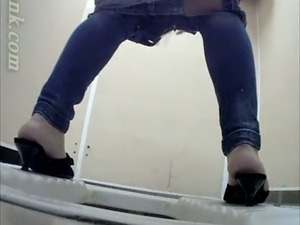 White brunette amateur chick in jeans pisses in the toilet
