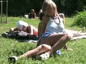 Beautiful and joyful blonde teen in the park flashes her pussy