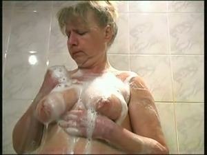 Mature blonde lady with big boobies takes a foamy shower for fun